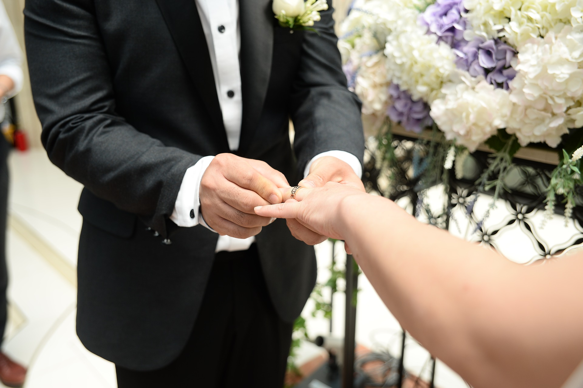 Man putting a ring on his bride's finger
