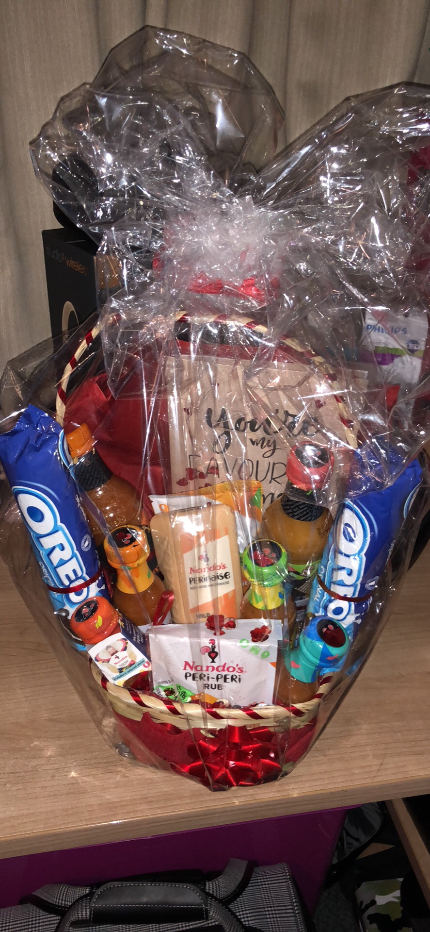 A hamper full of various Nando's sauces and vouchers, and Oreo cookies.