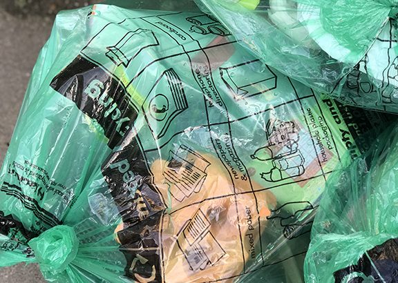 Green bags of recycling in a street