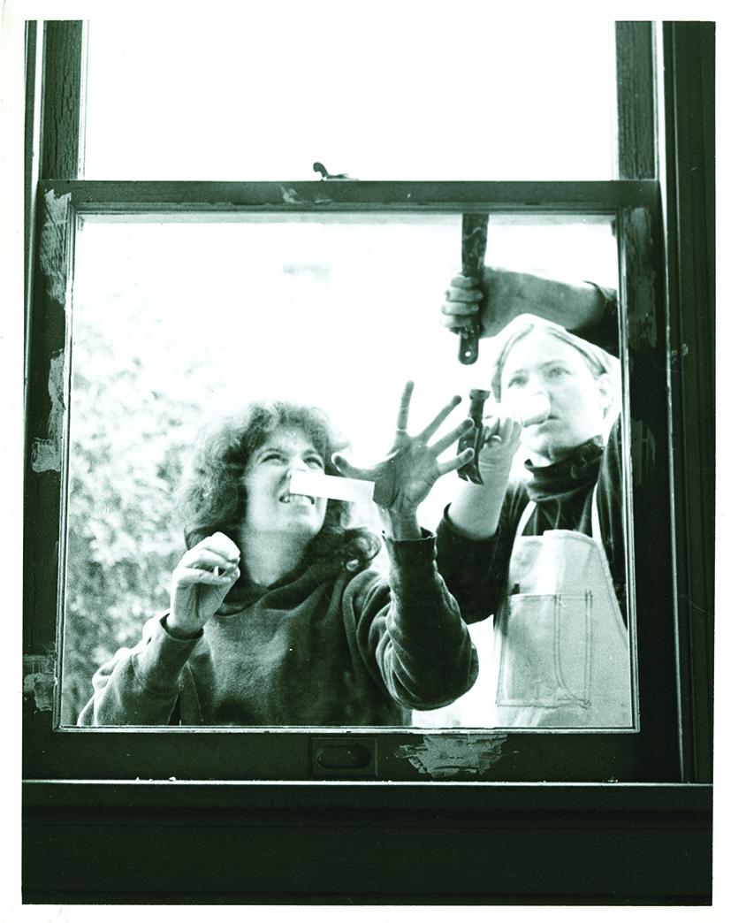 Two women working on a window