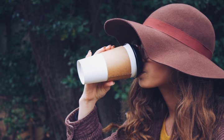 Lady drinks coffee from disposable cup
