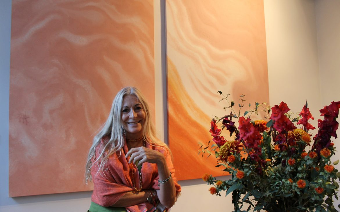 Rebecca Hossack in front of large coloured canvas