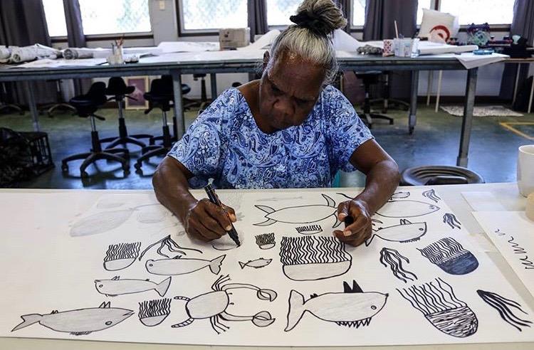 aboriginal artist sat at table drawing