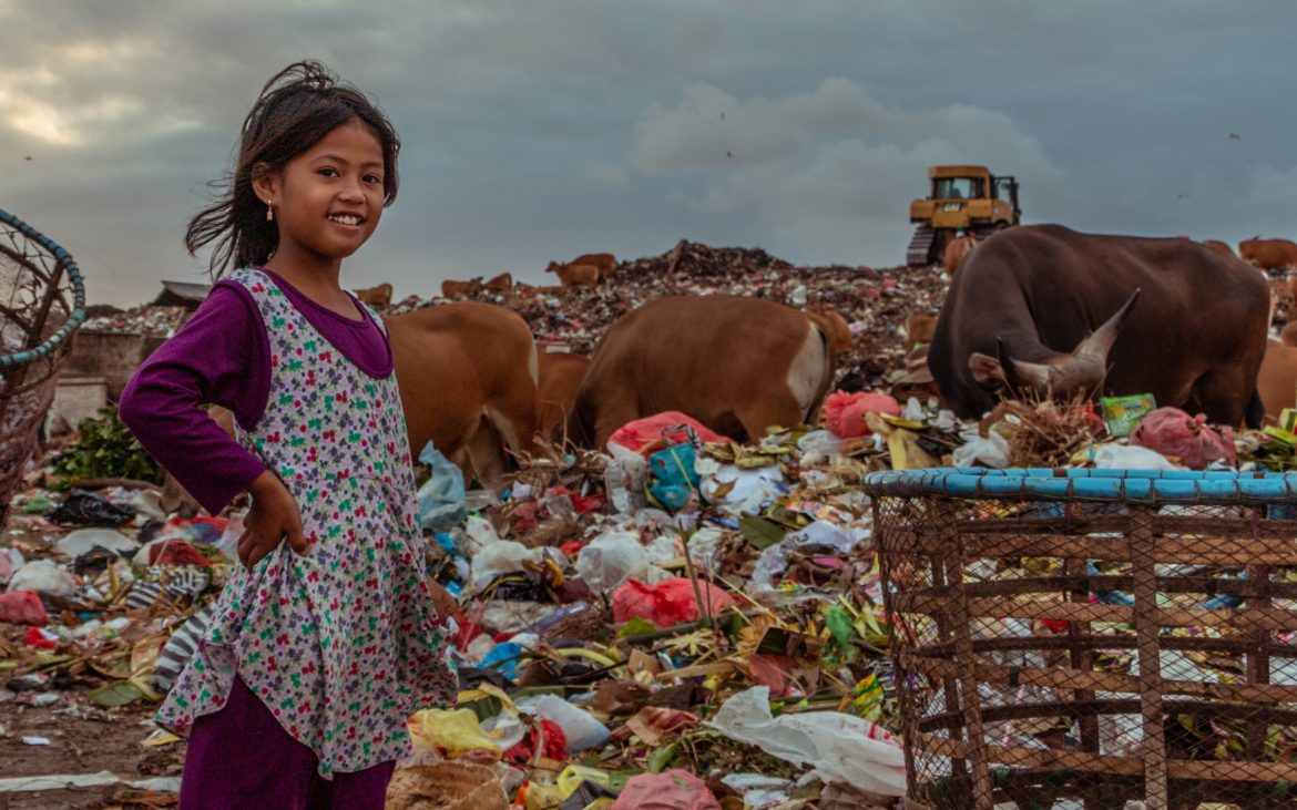 Girl standing in an Indonesian landfill site, a mound of plastics and cattle