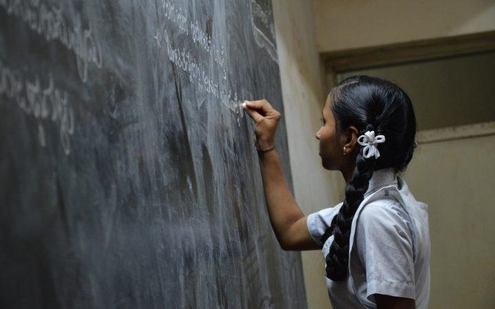 Young girl writing on blackboard with chalk