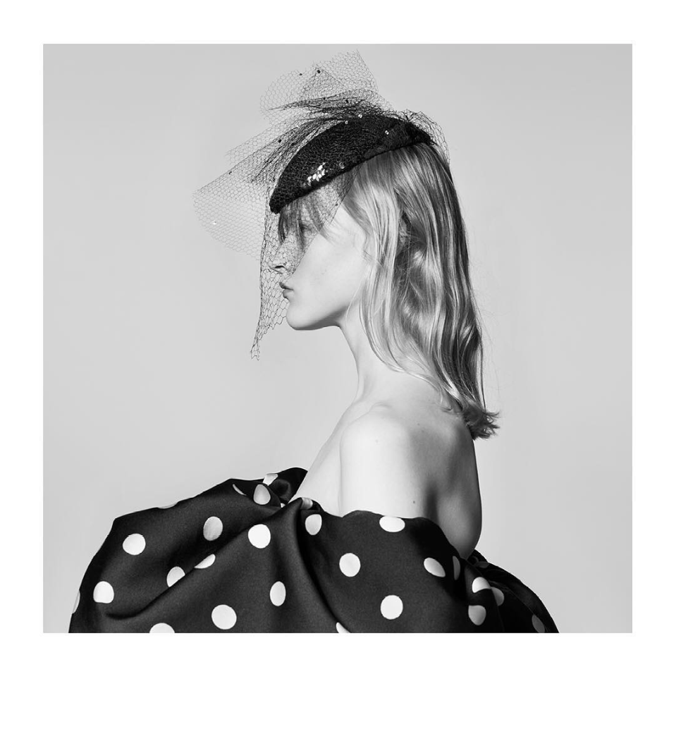 A black and white image of a model's side profile. She is wearing a hat and dress designed by Hedi Slimane for Celine's SS19 line.