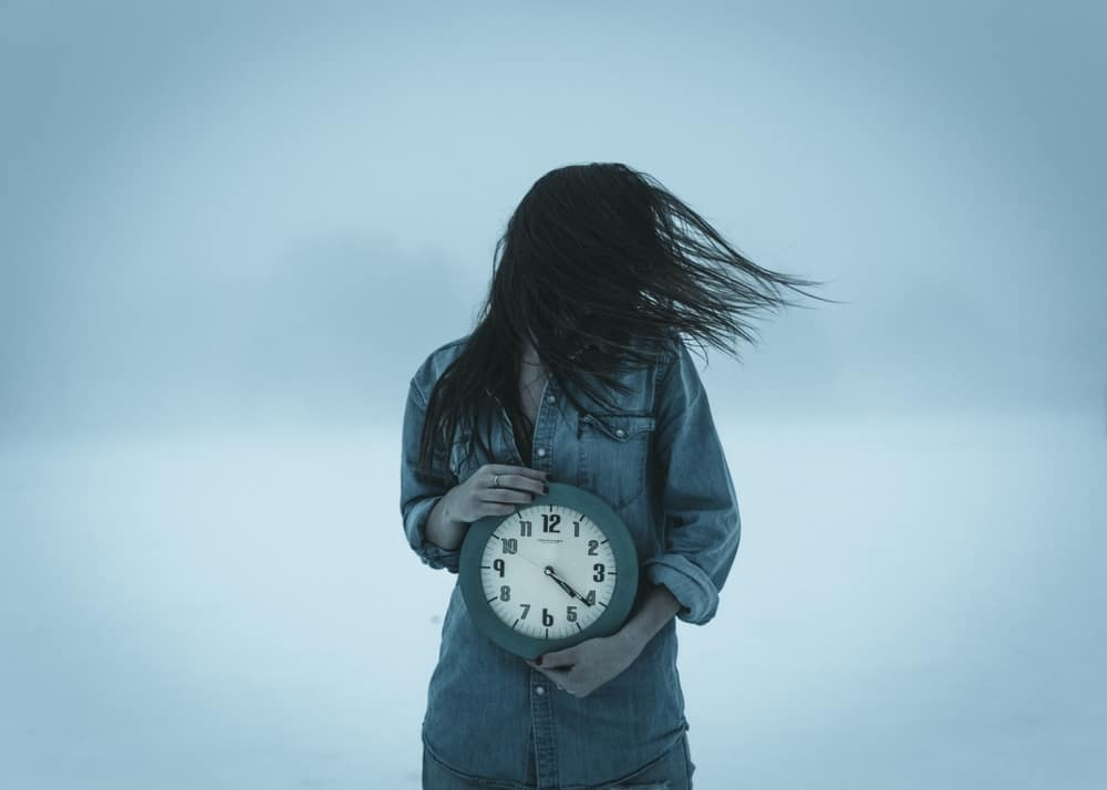 Lady holding a clock outside in the cold with hair blowing in the wind. Photo representing the fleeting time concept.