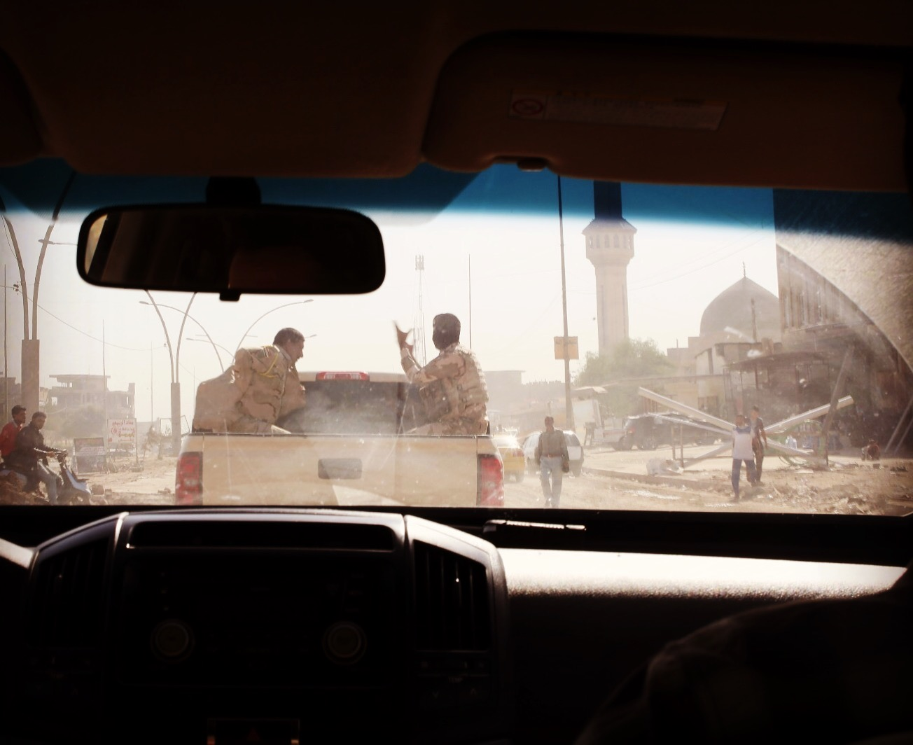 Mosul through a windscreen following a truck with soldiers in