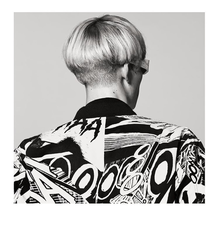 A black white portrait taken from the back of a model wearing sunglasses and a jacket designed by Hedi Slimane for Celine's SS19 line.