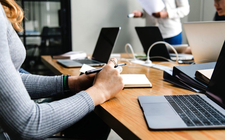 woman sat in a desk, laptop