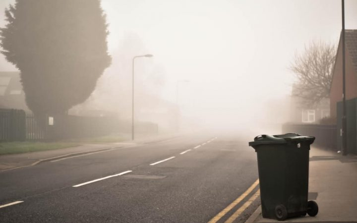 Misty morning with recycling bin next to road waiting for collection
