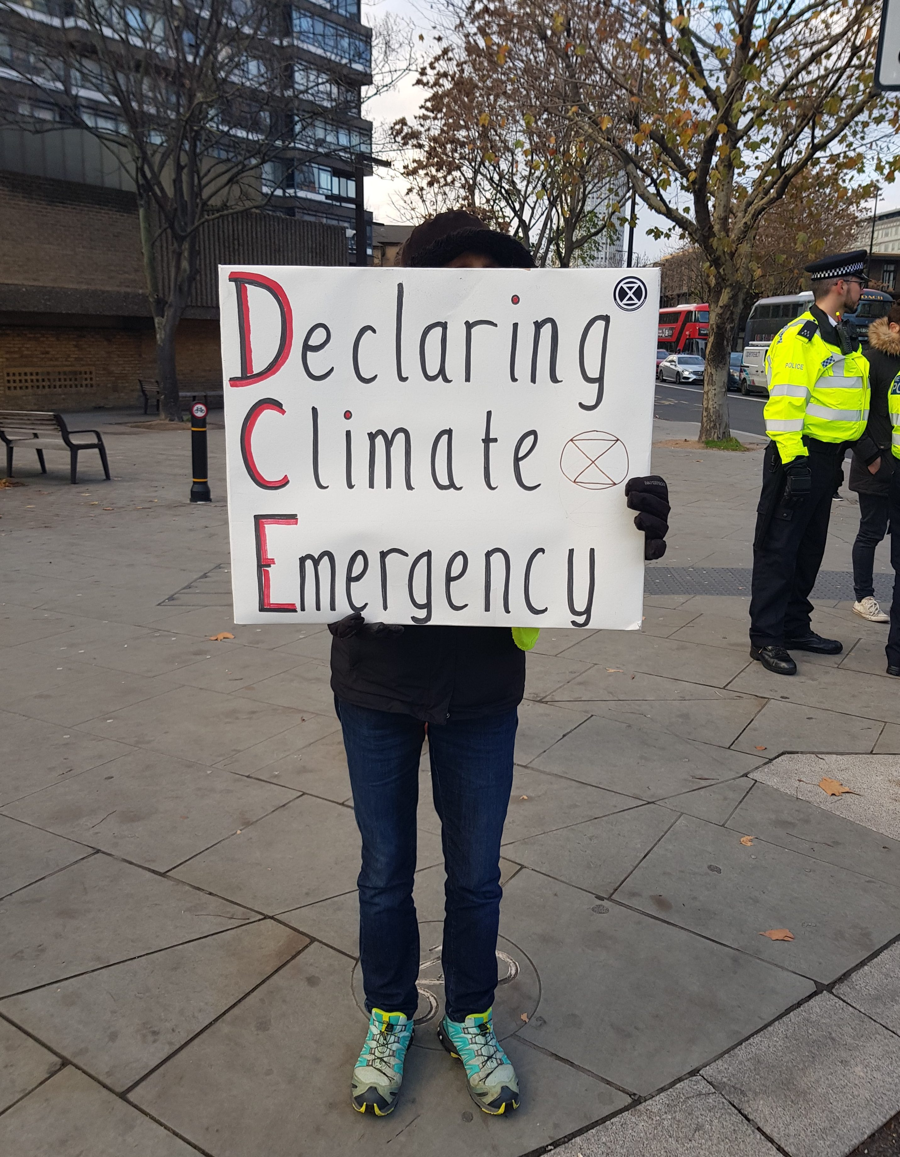 "Protester holding sign that reads ""Declaring Climate Emergency"""