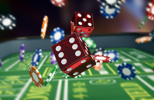 Rolling dice and casino chips on a roulette table.