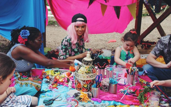 Three children engaging in arts and crafts with a Yellow Days charity member