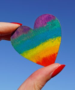 hand holding a rainbow coloured heart