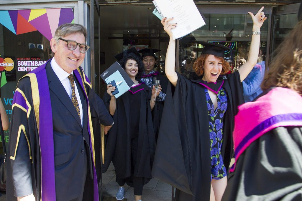 UAL students holding their diplomas smiling