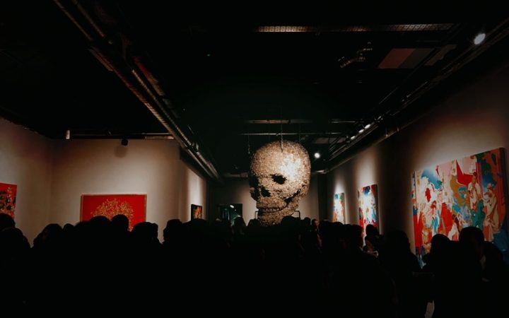 skull hanging from ceiling, silhouette of crowd in the foreground