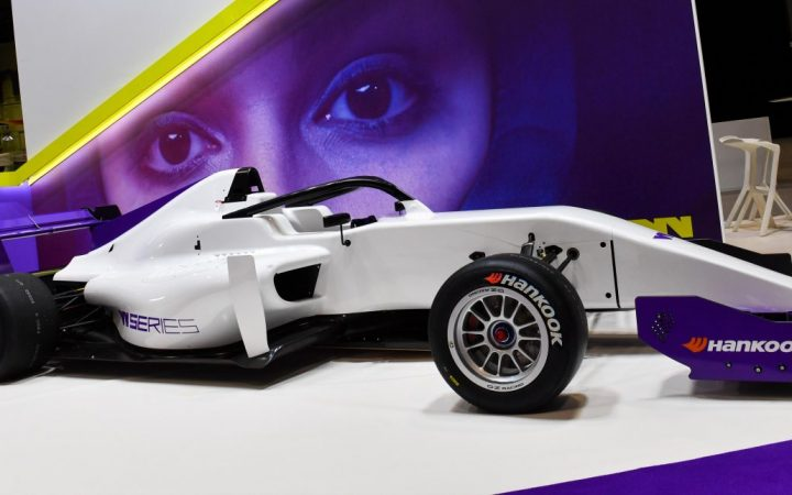 A photograph of the W series F3 car. A single seater with a white and purple body. Side view of the car.