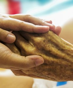 carer holding hands with an elderly person
