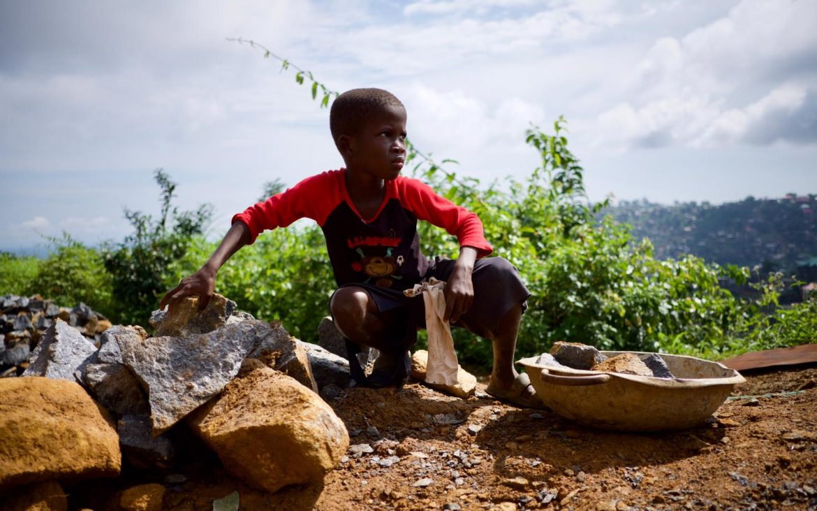 A young boy separates stone in a Freetown quarry