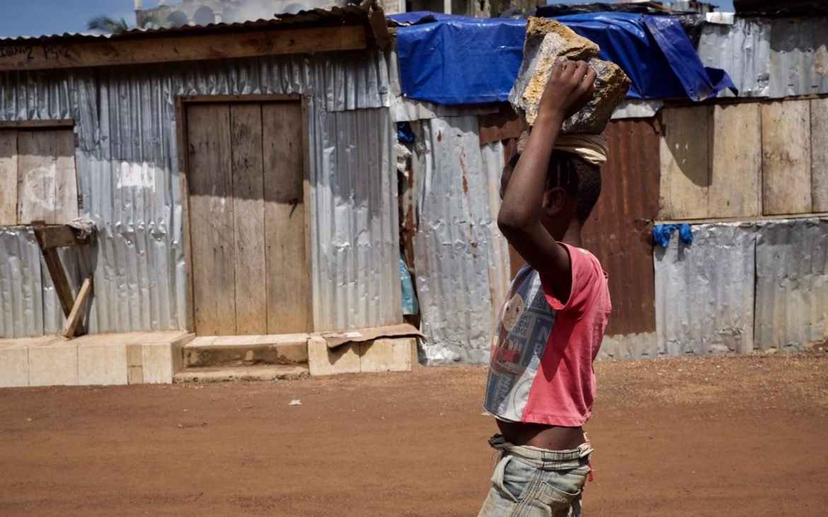 Young boy carrying stones on his head, ready to be broken in a stone quarry in Freetown.