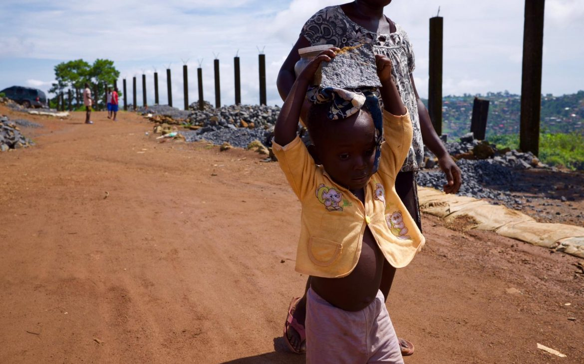 A three year old carrying a heavy rock on her head in a Freetown stone mining quarry.