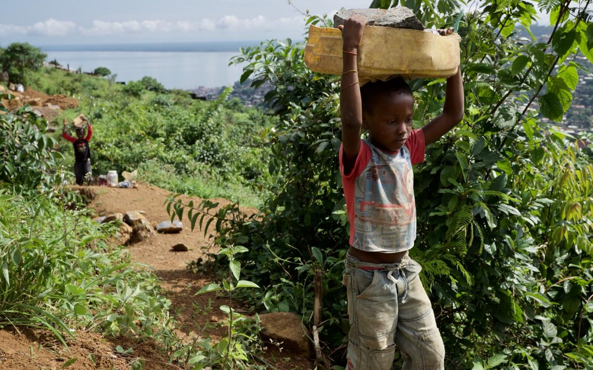 A young stone miner navigates a hillside quarry in Sierra Leone with rocks on his head.