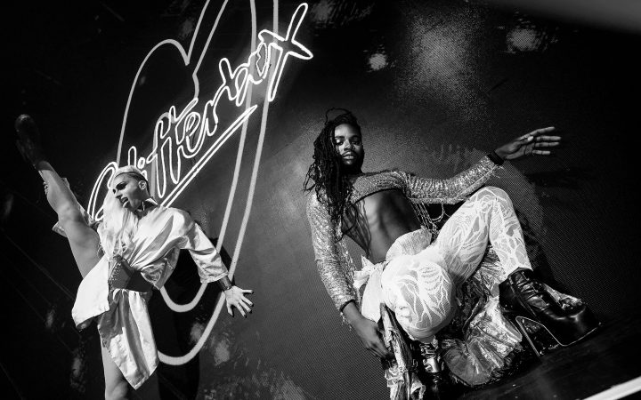 Performers dancing in front of a Glitterbox sign.