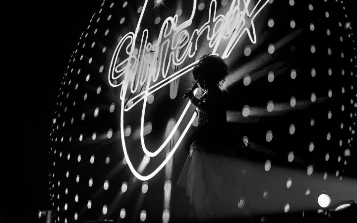 Black and white photo of Glitterbox performer in front of a Glitterbox sign