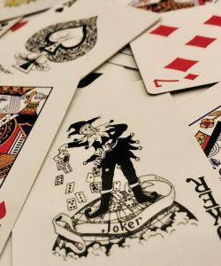 mix of poker playing cards; jblack joker card is shown in the foreground next to a king of hearts on the left and a queen of hearts on the right