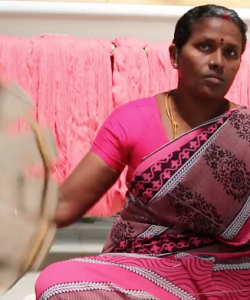Indian woman sat on the floor doing a pink handloom