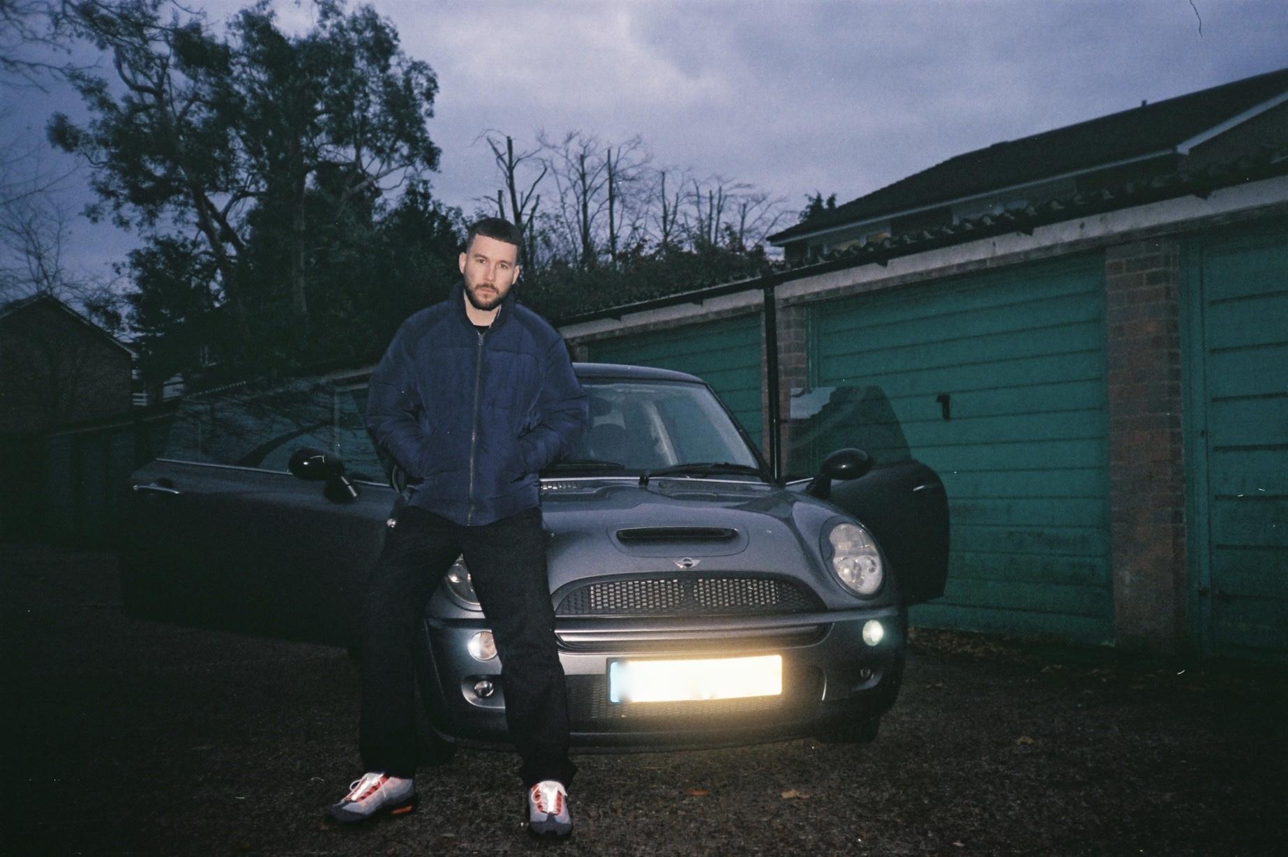 Jamie sits on his car