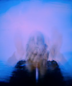 over exposure shot of a man. hands covering their eyes and face, blue and lavender tones.