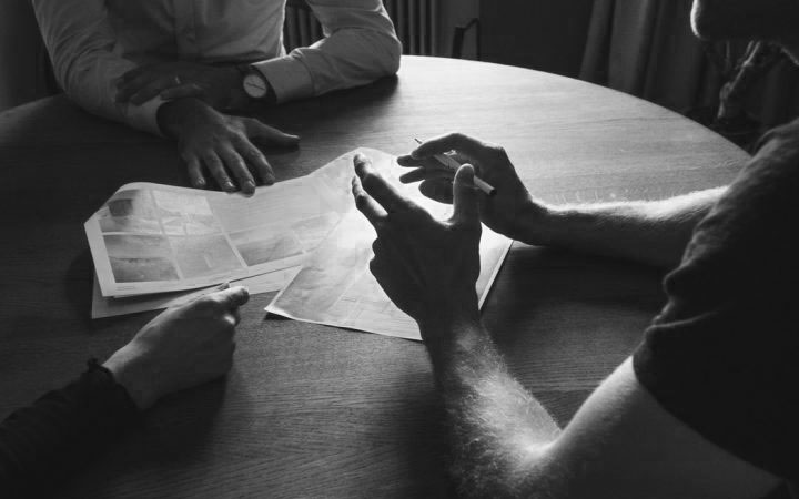 Low fi photograph of hands round a wooden table over paper work with the impression that they are discussing forms or are in a meeting
