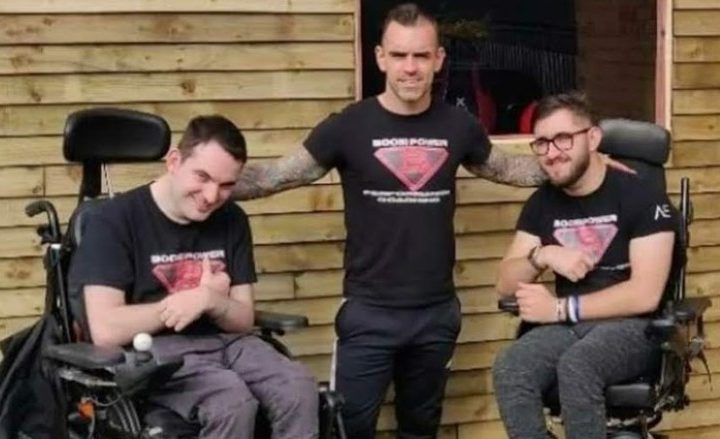 Head coach Glen is seen smiling with two of his clients who have cerebral palsy and are active members of the gym