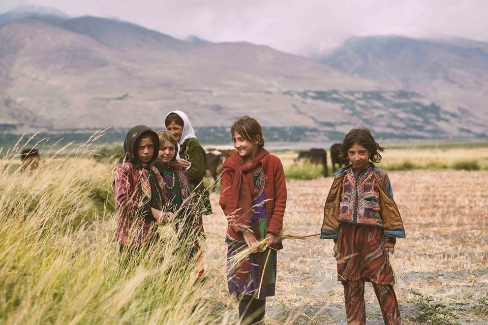 five children wearing traditional Afghan clothing standing in a field, with mountains in the background