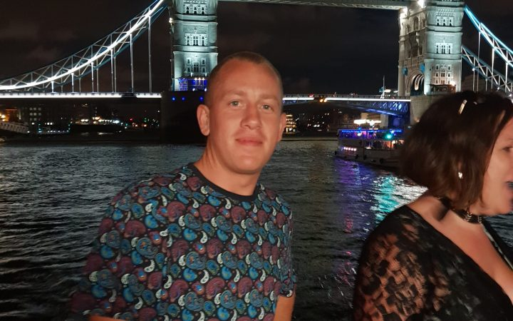 Caucasian male at boat party, a shoulder shot of him with river thames and tower bridge behind him, at night