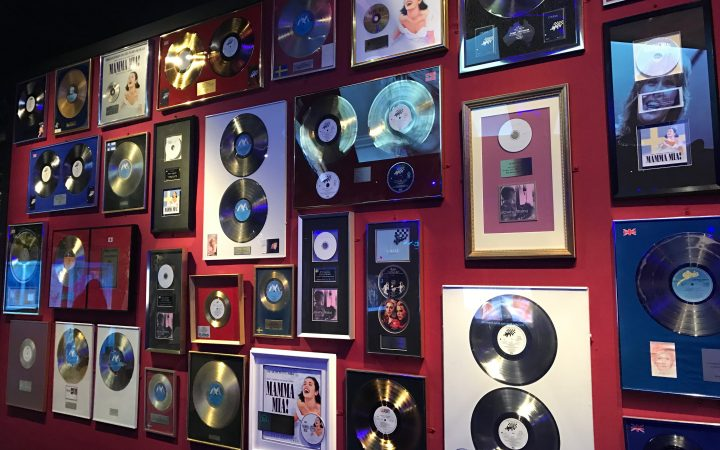 A photograph of the ABBA Museum wall decorated with pictures in photo frames and hanging records.