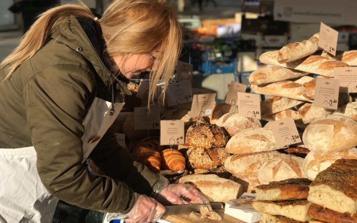 Woman cuts bread for tasters at the Breadwinners market stall