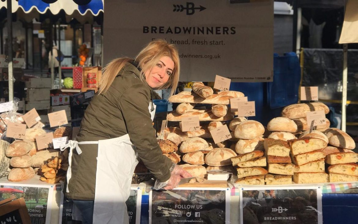 A woman cutting bread for tasters at the Breadwinners food stall