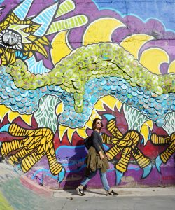 Patricia Nogueira walking near a colourful mural