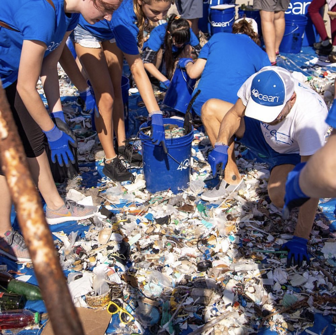 4Ocean volunteers gathered around plastic on the beach