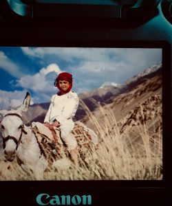 Local boy wearing a red turban and white dress, riding a monkey, cloudy sky and mountains in the background; image photographed of a canon camera