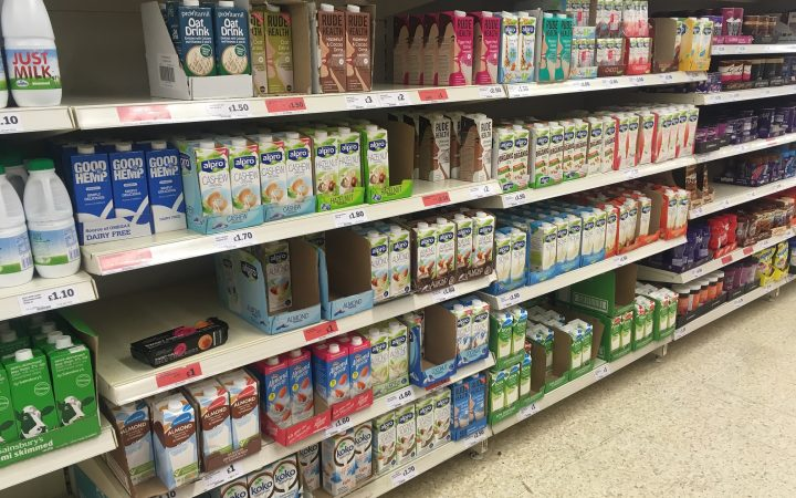 Aisle in a supermarket with shelves full of non-dairy milk