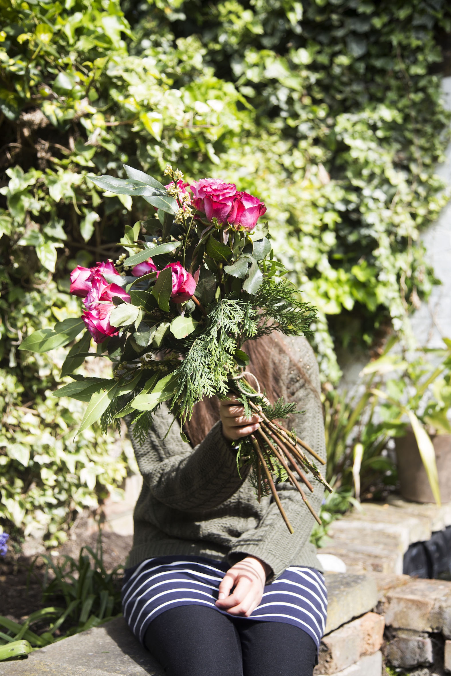 Girl covering her face with bunch of flowers