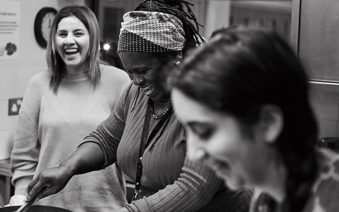 Three women smiling and cooking at Migrateful