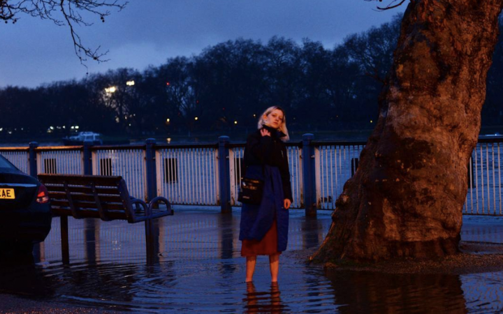Elizabeth stands in a puddle of flooded water by the Thames