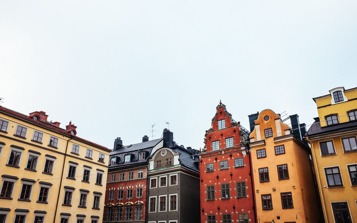 Photograph of the old town Gamla Stan. Mustard yellow and red brick buildings contrast with the grey sky.