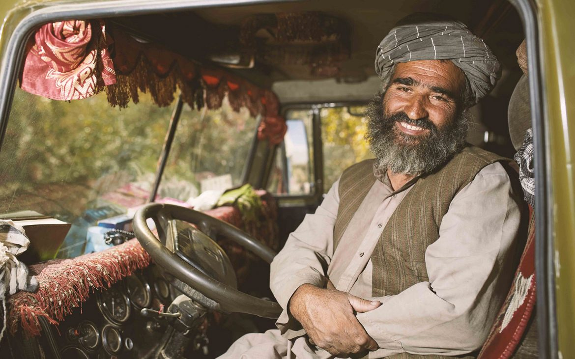man with beard and turban sitting in his truck, smiling
