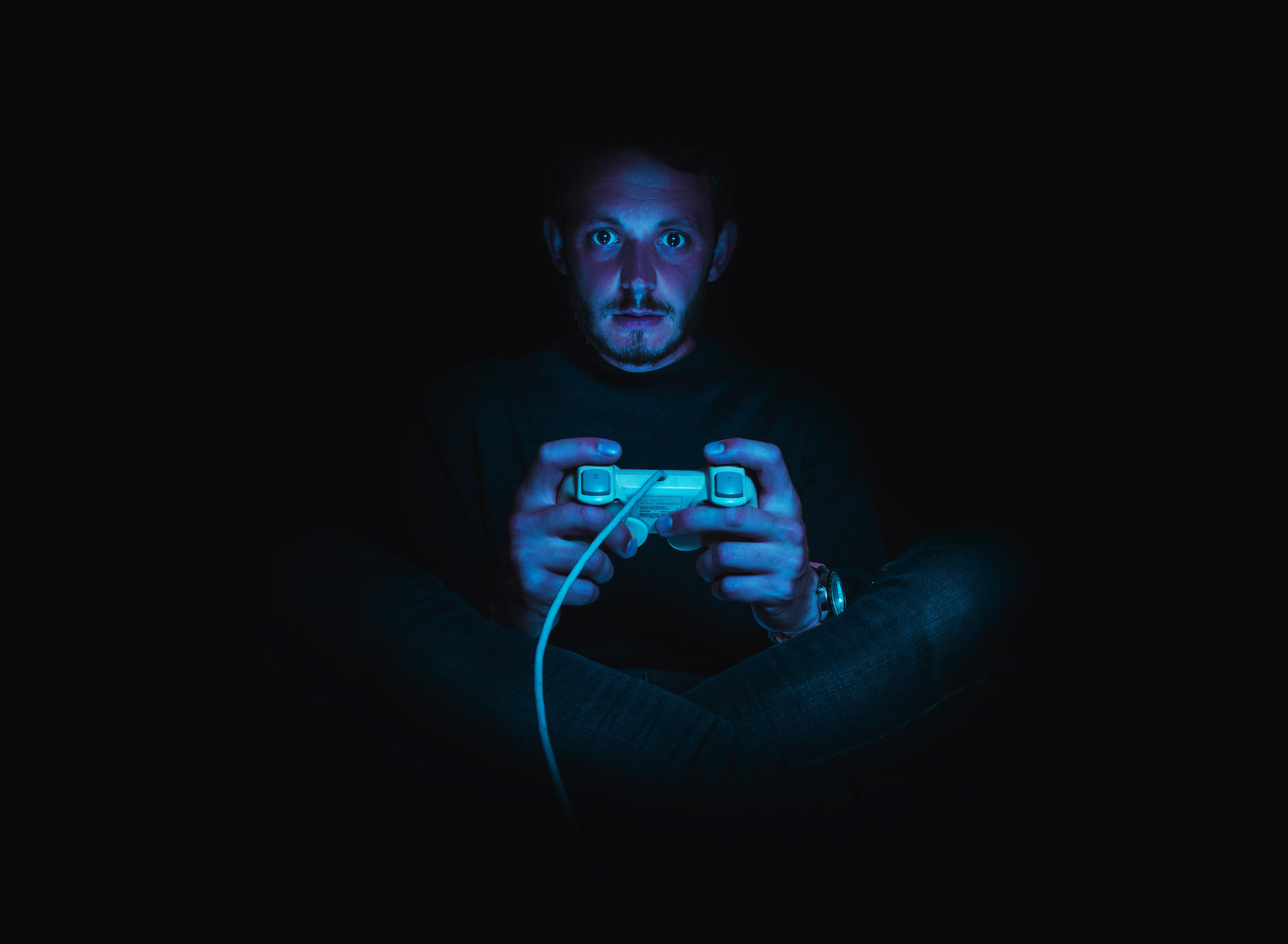 male gamer in dark room with a controller
